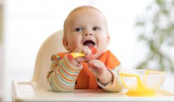 happy baby child boy waiting for food with spoon at table